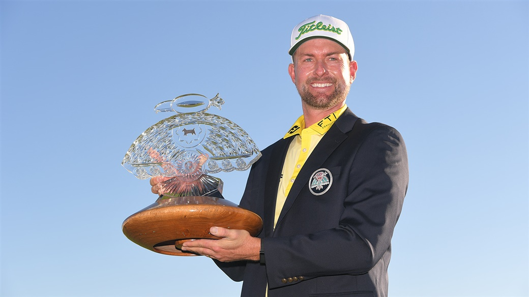 Webb Simpson raises the champion's trophy after winning the 2020 WM Phoenix Open.