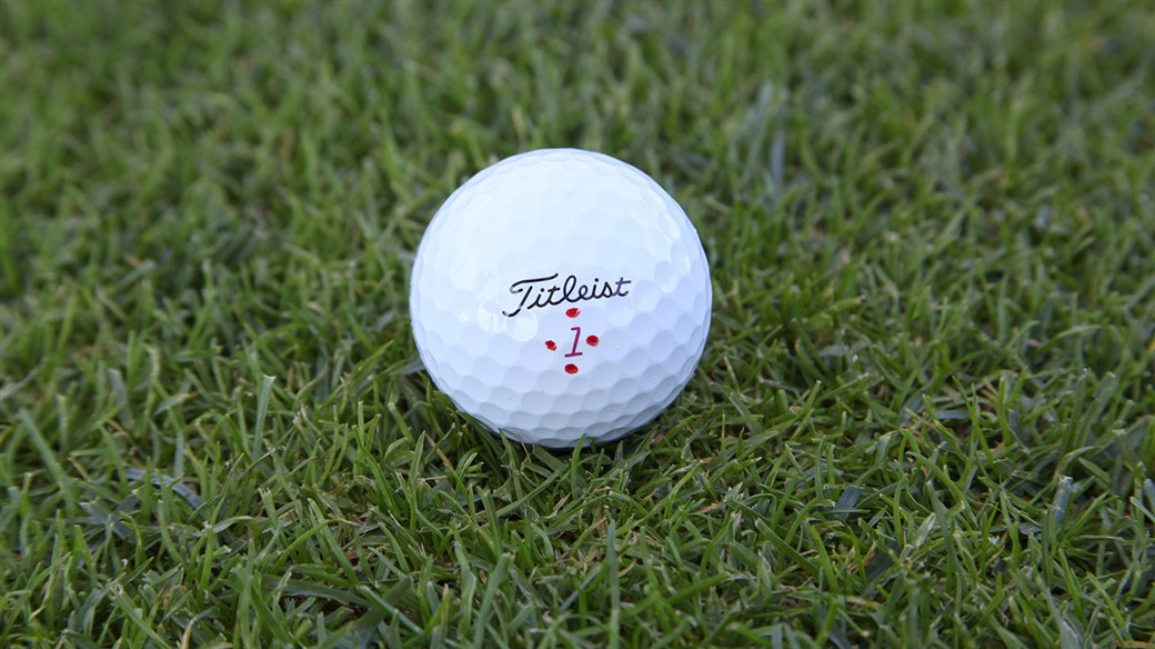 Justin Thomas's Pro V1x golf ball, marked with four Alabama Crimson dots around the play number