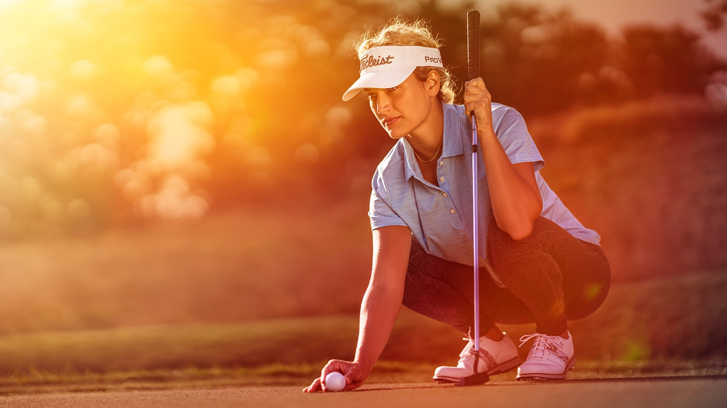 A golfer lines up a putt with her new Pro V1 golf ball